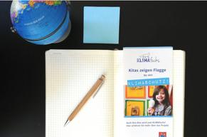 Aufsicht: Kleiner Globus mit Notizblock, Stift und KLIMAfuchs-Flyer