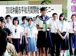 中学生大使を代表してあいさつする奥平茉那さん(美里中学2年)=1日午前、沖縄市役所