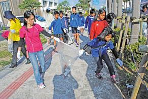 ボランティアで市街地の道路を清掃する人たち=17日午前、市役所通り