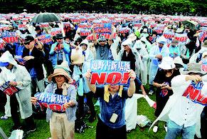 辺野古移設阻止を訴えるプラカードを掲げる大会参加者=11日、奥武山陸上競技場