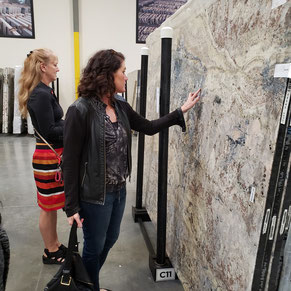 Tile Lines designers Lori and Heidi look at a granite slab in a slab warehouse.