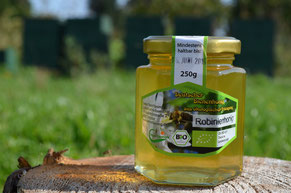 Der goldene Robinienhonig der Honigernte 2014 unserer Imkerei Ökohof Fläming vor den Bienenständen. Die Bienenkästen im Hintergrund sind grün, lediglich die Fluglöcher besitzen farbliche Markierungen.