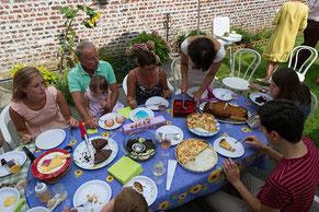 Une famille réunie pour un repas d'anniversaire dehors sur une terrasse dans un jardin