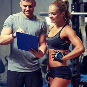 zwei Sportler besprechen in einem Fitnessstudio einen Trainingsplan