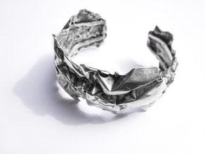 Un bracelet massif en argent au design froissé est posé sur fond blanc.