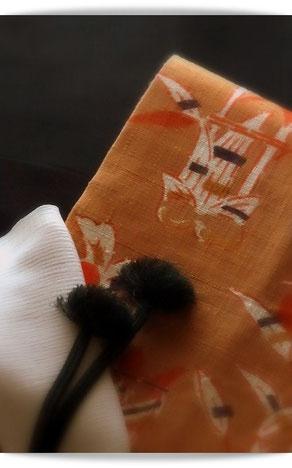 墨紺のきものは芝崎重一さんの座繰り紬。オレンジ色に生姜や糸巻が描かれた楽しい麻地の帯を合わせています。