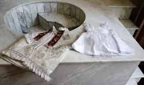 Tauf-Gewand für Jungen (rechts), Tauf-Kleid für Mädchen (links). Im Hintergrund ist das Taufbecken aus Marmor für Erwachsene zu sehen. Foto: Jennifer Peppler