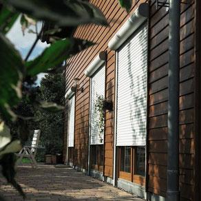 Grüne Vorbaurollläden an der Terrassenseite eines Einfamilienhauses