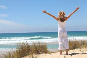 Frau blickt am sommerlichen Strand aufs Meer und breitet die Arme aus