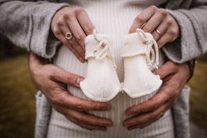 Kreatives Babybauchfoto mit Strickschuhen und Händen inszeniert von der Familien Fotografin Monkeyjolie