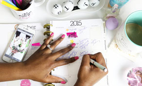 Eine Frau schreibt Termine in einen Kalender