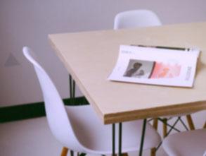 Ein Konferrenztisch mit zwei Stühlen. Ein Buch liegt auf dem Tisch.