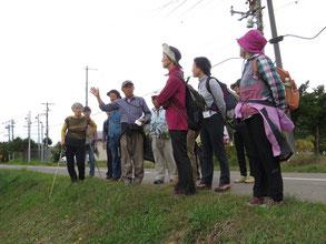 高橋さんからブドウ栽培の説明を聞いています。