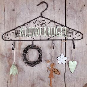 """Wanddekoration in Form eines Kleiderbügels mit 4 Haken und Anhängseln. Bild trägt die Aufschrift """"Kleiderbügel""""."""