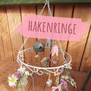 """Weißer Ring mit Schnörkeln und Haken und diversen dekorativen Anhängseln wie Windlichter und kleine Flaschen. Bild trägt die Aufschrift """"Hakenringe""""."""