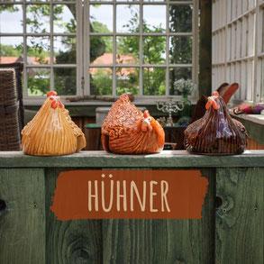 Drei Hühner aus Keramik in verschiedenen Brauntönen sitzen auf einer Terrasse mit alten weißen Fenstern im Vintage-Look.