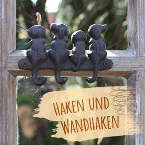 """Wandhaken aus Gusseisen in Form eines Hahns mit Schnörkeln vor einer grauen Holzwand. Bild trägt die Aufschrift """"Haken und Wandhaken""""."""