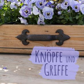 """Gusseiserne Knöpfe in Form von Blüten mit Hintergrund aus Holz. Foto trägt die Aufschrift """"Knöpfe und Griffe""""."""