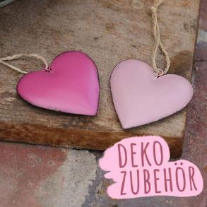 """Drei bauchige Blechherzen in Rosa und Pink mit Jutekordel auf Holztisch mit Metallrahmen. Foto trägt die Aufschrift """"Zubehör""""."""