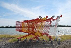 Vier Einkaufswagen in rot, gelb und weiß