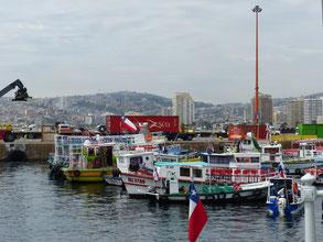 Au port, il y a des bateaux de plaisance colorés et on peut apercevoir derrière, des bâtiments et des colines