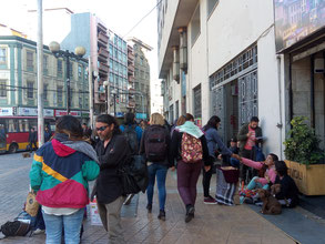 Scène de vie représentant des passants et des personnes assises par terre qui vendent on ne sait quoi