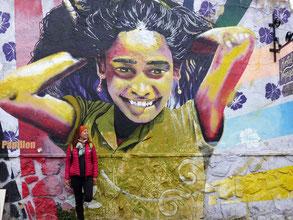 graffiti d'une jeune fille souriante et moi adossée au mur