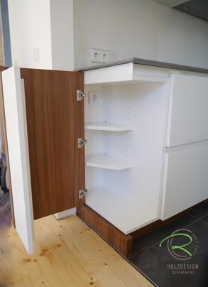 Moderne Küche in weiß und Nussbaumdekor von Schreinerei Holzdesign Ralf Rapp in Geisingen mit Eck-Stauraumlösung Inneneinteilung im Unterschrank für Handstaubsauger mit Ladestation