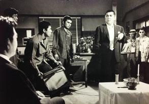 暴力団・組長 鶴田浩二(左端)に向って吼える若山富三郎。ふたりの間に小林捻持と曽根晴美が居る。右端がサングラスに帽子姿の子分役・竹垣悟。若山富三郎が拳銃を後ろに放った時、受け取ったのが今では良い思い出だ。