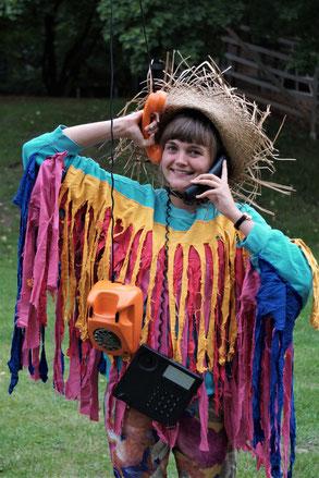 Laura, lächelnd, mit Strohhut, buntem Fransen-Papageien-Kostüm und mehreren Telefonen in den Händen und an den Ohren