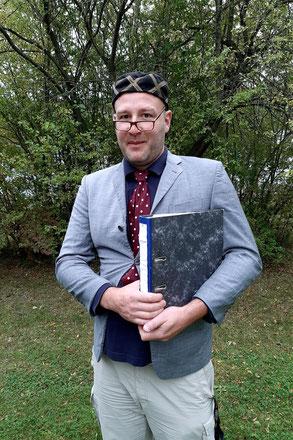 Ben in zu kleinem grauen Jackett, mit rot-gemusterter Krawatte, tiefsitzender Brille, seltsamer Mütze und einem Aktenordner unter dem Arm