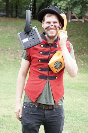 Simon, lachend mit roter Pagen-Weste, Hut und mehreren Telefonen