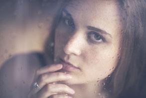 Junge natürliche Frau mit blauen Augen und langen roten lockigen Haaren, direkter Blickkontakt in die Kamera, Close-up-Porträt, Nahaufnahme vom Gesicht, blauer Schal mit weißen Sternen