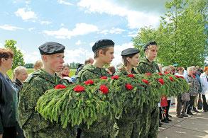 Волонтеры школы № 606 возлагают гирлянду памяти на братском захоронении в Кондакопшино