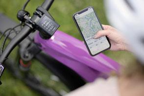Frau mit e-Bike und Bosch Smart System Flow App in der Hand