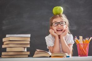 Mädchen zwischen Büchern und einem Apfel auf dem Kopf