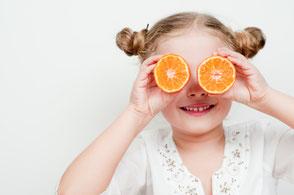 Mädchen hält sich Orangen vor die Augen