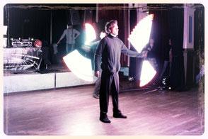 LED stäbe und Pois werden neben Leuchtkeulen jongliert.