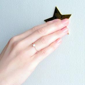 女性の手に星のお守りK10ゴールドリングを着用している画像