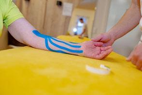 Kinesio Tape Mit Hilfe von elastischen, bunten Klebestreifen, die in speziellen Techniken auf die Haut (Gelenke, Muskeln, Bänder, Nerven) aufgeklebt werden, sollen unter anderem die Durchblutung verbessert, sowie Gelenke stabilisierend unterstützt werden.