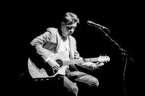 Gitarrist Julian Wolf stimmt seine Gitarre während eines Konzertes in der Dresdner Neustadt.