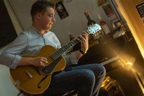Gitarrist und Musiker Julian Wolf mit einer Akustikgitarre von Epiphone während eines Konzertes in Meißen