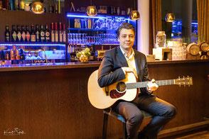 Gitarrist und Musiker Julian Wolf mit Anzug und Gitarre in der Dachbar des QF Vienna House Hotels Dresden.