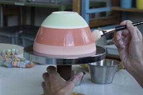 Geschützter Arbeitsplatz der Keramikwerkstatt. Bemalen einer Keramikschale auf einer Drehscheibe.