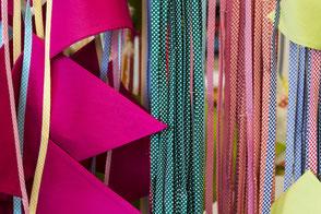 Zuschneiden von farbigen Stoffen in der Textilwerkstatt an geschützten Arbeitsplätzen.