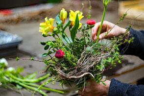 Binden von Blumengestecken und pflanzen von Kräuter-Setzlingen. Arbeitstraining in der Gärtnerei.