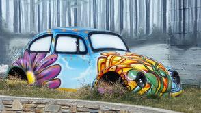 Alter VW-Käfer, ohne Räder, fröhlich bemalt.