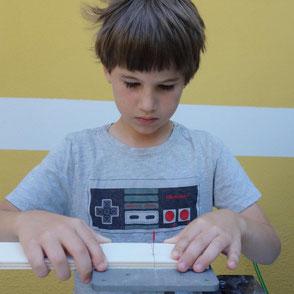 Ein Junge schneidet mit einem cool tool Werkzeug