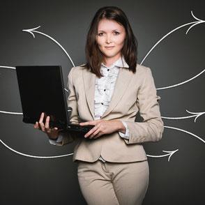 Link zu Wiedereinstig für Frauen; Eine Frau steht mit Laptop in der Hand vor einer Tafel, auf der Pfeile zu sehen sind.