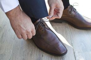 saarclean, Schuhreparatur-Service, Geschäftsmann bindet sich die Schuhe